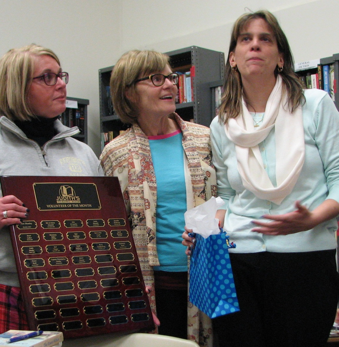 Dawn Bush (right) is recognized  on a plaque that hangs in the Judith's Reading Room HQ in Bethlehem. Cathy Leiber (middle) is the President of Judith's Reading Room.